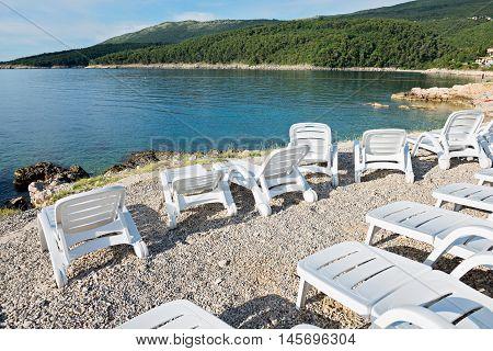 Pebble beach, chaise-longues and bue sea in Istria, Croatian coast