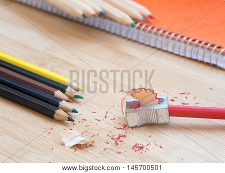 Color art pencils with sharpener and notebook. Back to school concept