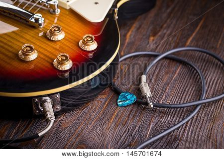 Electric guitar guitar connected with a cable on wooden table close up