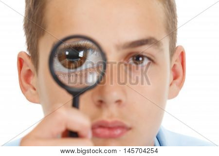 Caucasian guy looking through a magnifying glass with fish eye lens isolated on white