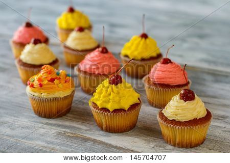 Bright frosted cupcakes. Pastry on gray wooden background. Sweet wonders of cooking. Guess the taste.