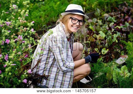 Portrait of young blonde woman gardener cares for the plants in garden, stylish country image