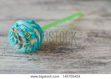 Ball-shaped candy with sprinkles. Light blue icing. Cake pop for dessert. Brand new taste.