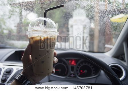 transportation and vehicle concept - hand of man holding a take away cup of iced coffee while parking the car with water drop of raining,boost the energy to drive