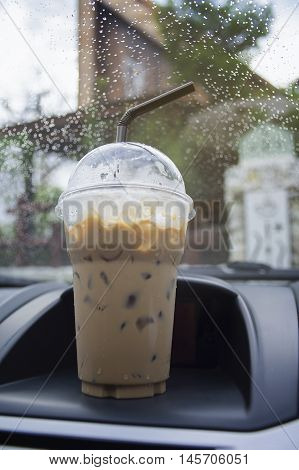 transportation and vehicle concept - take away cup of iced coffee put on a front console of a car with water drop of raining,boost the energy to drive
