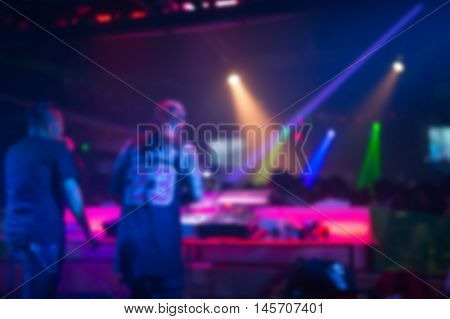 Blurred background : Club disco DJ playing and mixing music for crowd of happy people. Nightlife concert lights flares