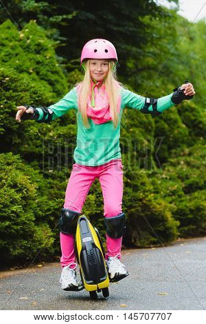 Happy girl riding on mono-wheel hoverboard or gyroscooter outdoor.