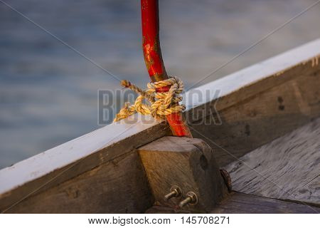 Close-up of a mooring rope with a knotted end tied around a cleat on a wooden pier. Nautical mooring rope
