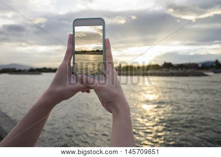 Close up of woman's hand holding smart phone mobile smart phone over blurred beautiful sea with sunset moment to take a photo of the sea,selective focus,filtered image