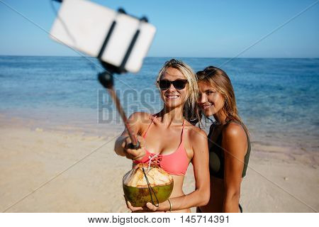 Two young women in swimsuit on the beach taking self portrait with smart phone on selfie stick.