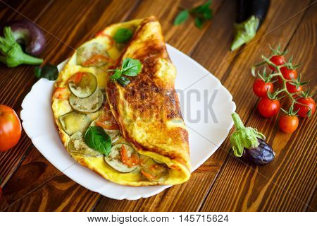 fried omelet with eggplant and tomatoes on a wooden table