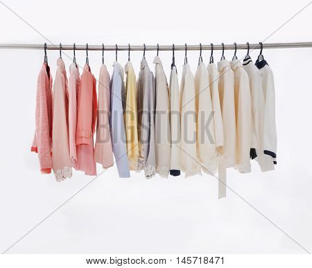 Set of l female clothes of different colors on hangers