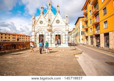 Pisa, Italy - June 02, 2016: Santa Maria della Spina cathedral with tourists on the riverside in Pisa town in Italy