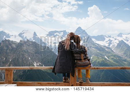 Mom with daughter relaxing in the rustic wooden terrace on mountain, alpine view, snow on hills. Dombay, Karachay-Cherkessia, Caucasus, Russia.