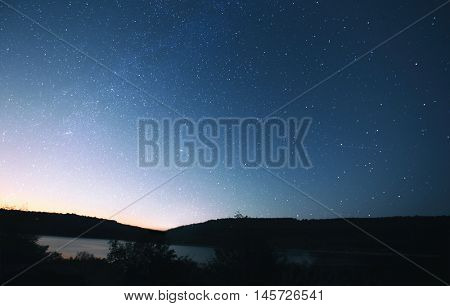 The beautiful night sky with muck of stars and the forest and lake on foreground