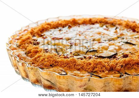 Close-up of homemade crustless zucchini quiche baked in a glass fluted dish isolated on white