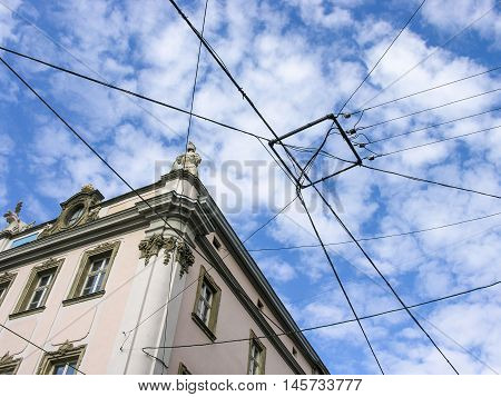 Many wires are crossed in the sky over the heads of people walking in the city center