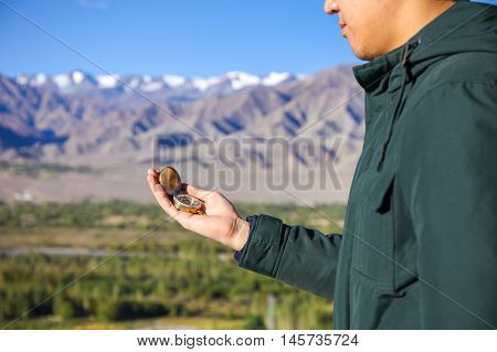 Young Traveler Looking At Compass In Himalaya Mountain View Background