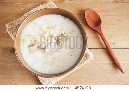 Traditional chinese porridge rice gruel in brown bowl with wooden spoon on wood table