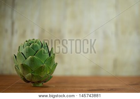 A ripe green artichoke sitting on a wood table.