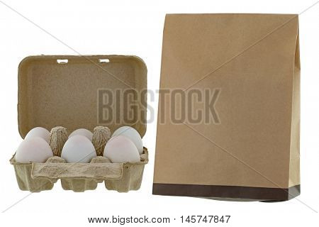 Paper pulp egg tray packages of fresh eggs next to brown recycled paper bag isolated on white background