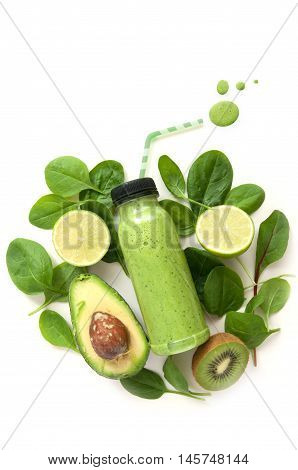 Bottled detox drink surrounded by green food ingredients with juice drops spilling out of a straw