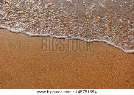 Golden sand and wave background a lot of space for text from above view.