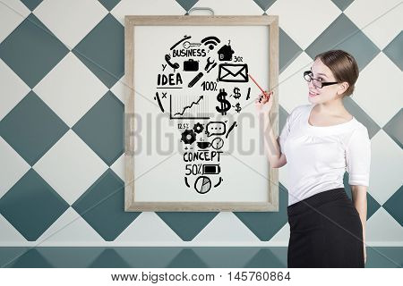Young businesswoman giving presentation on business with lightbulb sketch in picture frame. Chessboard wall background. Idea concept