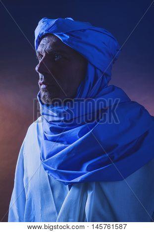 Side View Of Berber Man In Night Light Wearing Blue Turban With White Robe. Studio Shot.