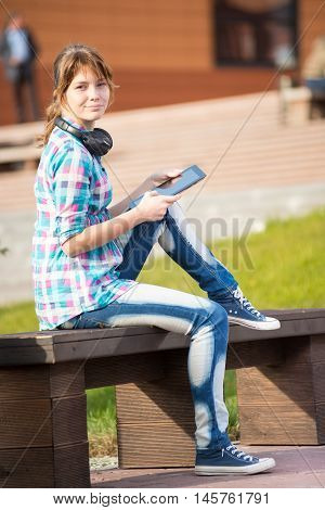 Preparing to exams outdoors. Beautiful young female student writing or reading something from note pad.  Woman sitting on bench in city park.