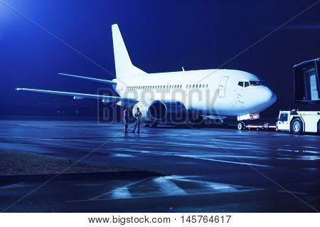 Airplane docked at the terminal and ready for takeoff. Modern international airport at night.