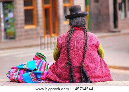 Local woman sitting at Plaza de Armas in Cusco Peru. In 1983 Cusco was declared a World Heritage Site by UNESCO poster