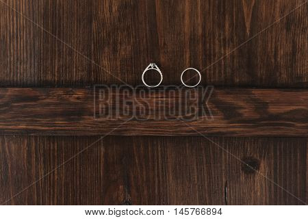 Wedding rings on a wooden background, original composition