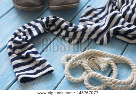 Frock and rope on a blue shabby wooden table.