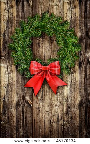 Christmas wreath from pine twigs and red ribbon bow on wooden background