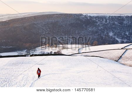 Woman walking in snow covered countryside Peak District UK