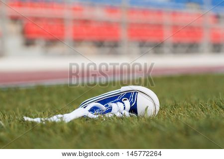 1 sneakers lying on a football field. Concept of losing, tired, defeated, fall, pain