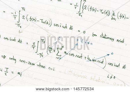 Maths homework showing handwritten mathematical formulae on paper