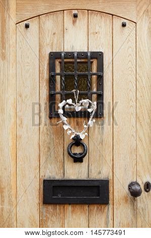 Traditional wooden front door of a house with ironmongery