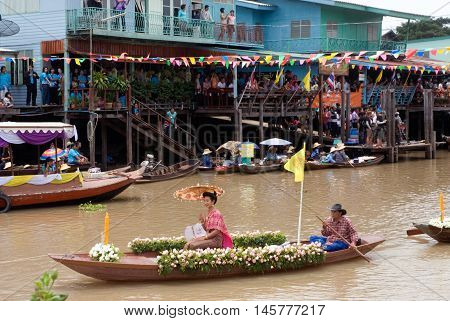 AYUTTHAYA, THAILAND - JULY 15, 2011: Pretty woman sitting show on the flower boats in candle floating parade, the unique annual candle festival of Buddhist lent  in Lad Chado, Ayutthaya, Thailand.