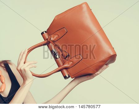 Elegant fashionable woman with leather handbag. Stylish girl holding brown bag. Female fashion vogue. Studio. Instagram filter.
