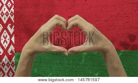 With a stylized Belarusian flag background an anonymous person's hands being held in the form of a heart, symbolizing love and patriotism for Belarus.