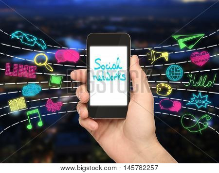 Hand holding cellular phone with text on screen and colorful media icon on city background. Social networks concept