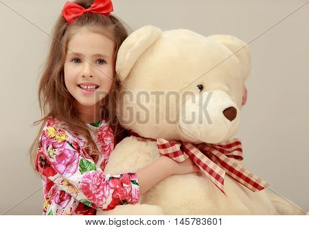 Gentle little girl with a long ponytail down to his shoulders, and a red bow on her head, in a beautiful summer dress. Girl hugging a big Teddy bear. Close-up