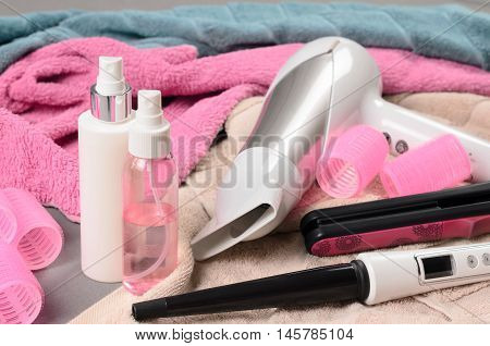 Hair Styling Tools (white Hairdryer, Hairspray, Curler, Spray, Cone Curling Wand) On Beige Towel