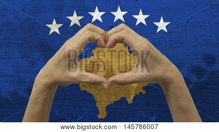 With a stylized Kosovan flag background an anonymous person's hands being held in the form of a heart symbolizing love and patriotism for Kosovo.