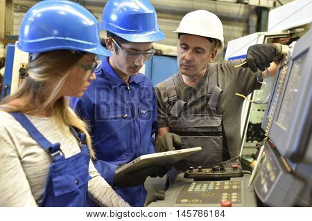 Metalworker with training people using electronic machine