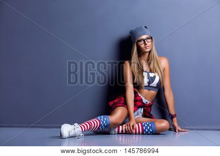 glamor sexy smiling beautiful young woman model in sport shirt and hat and Red checkered shirt, stylish glasses, red wristlet watch, white sneakers, leggings with USA flag, leaned on textured wall