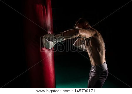 Muscular hipster fighter giving a forceful kick during a practise with a boxing bag. Kickboxing.