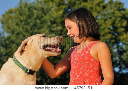 cheerful little girl playing with a cute dog outside